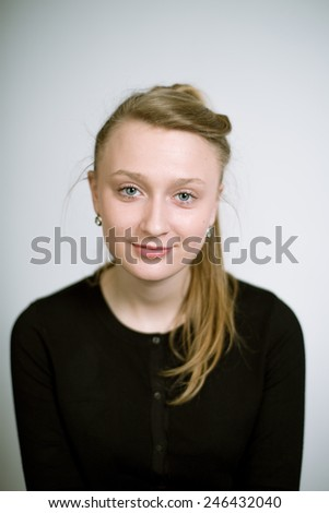 Portrait of a real young smiling woman on a light background in a black cardigan. Shallow depth of field. Focus on the eyelashes - stock photo