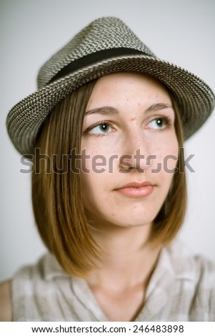 Portrait of a real young woman on a light background in a linen shirt and hat. Shallow depth of field. Focus on the eyelashes