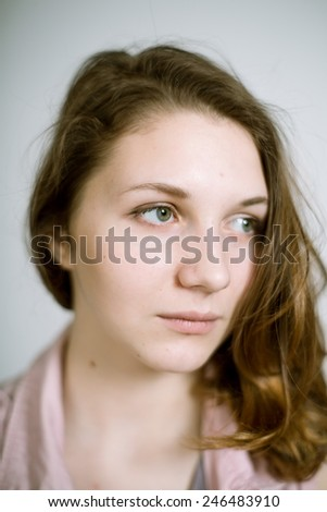 Portrait of a real young woman on a light background in a pink denim vest. Shallow depth of field. Focus on the eyelashes
