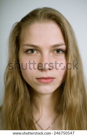 Portrait of a real young woman on a light background in a white shirt. Shallow depth of field. Focus on the eyelashes