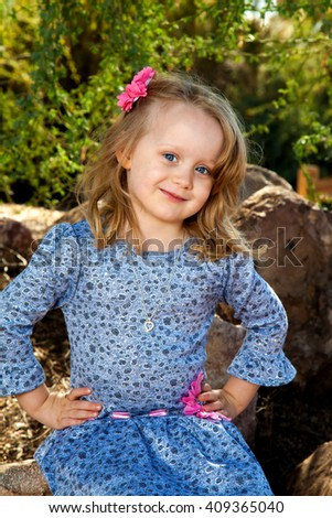 Portrait of a really cute little blond girl with big blue eyes and hands on her hips.  She is wearing blue with pink embellishments - stock photo