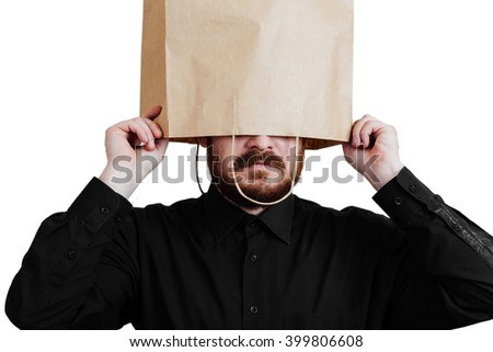 Portrait of a red-bearded, balding male brutal. White isolated background. Black shirt and pants. Paper bag over head. Half face closed package - stock photo