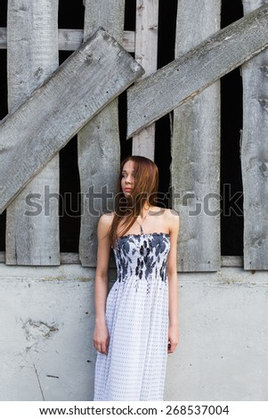 Portrait of a red-haired pretty young woman in floral dress looking at camera. Hair moving from wind - stock photo
