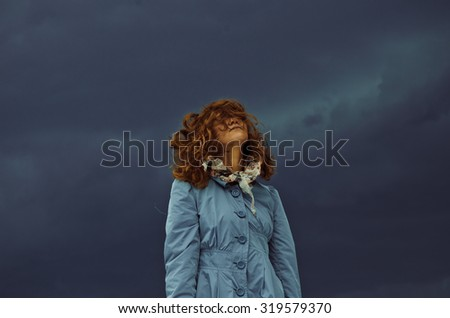 portrait of a red haired woman standing alone under a stormy gloomy dark blue sky - stock photo