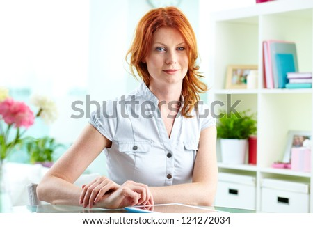 Portrait of a red-haired woman using a tablet computer indoor