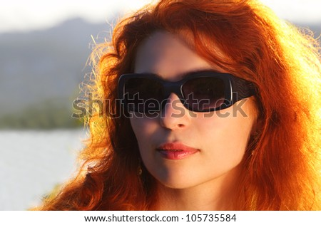 Portrait of a red haired woman wearing sunglasses in the sunny evening - stock photo