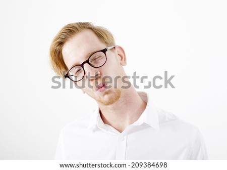 Portrait of a red-haired young man in a white shirt with puckered lips