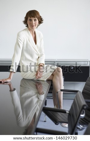 Portrait of a redhead businesswoman sitting on table in conference room - stock photo