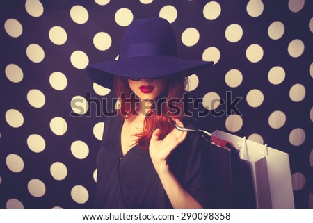 Portrait of a redhead girl with shopping bags on black polka dot background. - stock photo