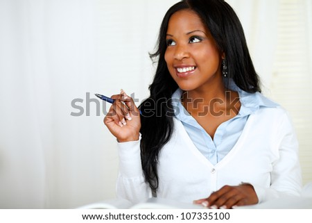 Portrait of a reflective young woman smiling and studying at soft colors composition - stock photo