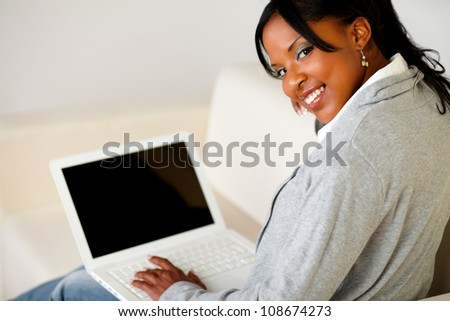 Portrait of a relaxed afro-American female browse the Internet on laptop while is sitting on sofa at home indoor and is looking to you