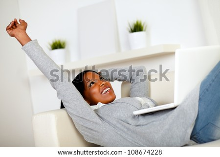 Portrait of a relaxed afro-American woman browsing the Internet on laptop while is lying on sofa at home indoor - stock photo