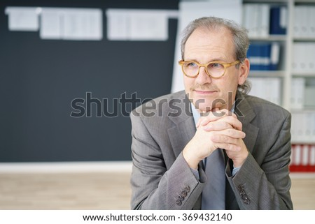 portrait of a relaxed businessman folding his hands looking to a side in thoughts - stock photo