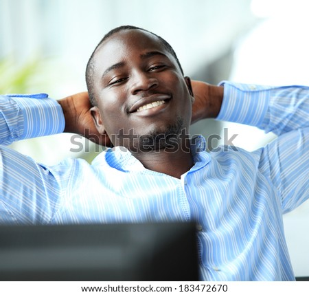 Portrait of a relaxed businessman looking away. african american businessman daydreaming in office   - stock photo