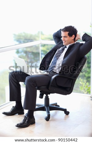 Portrait of a relaxed businessman sitting on an armchair working with a laptop in his office - stock photo