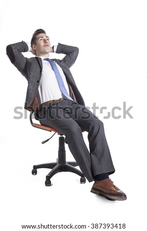 Portrait of a relaxed businessman sitting on chair over white background.