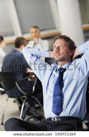 Portrait of a relaxed Businessman with meeting in the background - stock photo