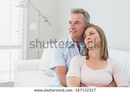 Portrait of a relaxed couple embracing in the living room at home