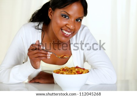 Portrait of a relaxed female looking at you and having breakfast at soft colors composition - stock photo