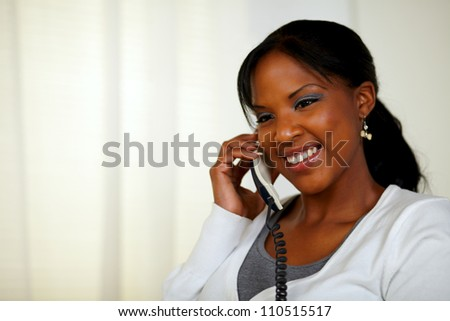 Portrait of a relaxed female smiling and conversing on phone at soft colors composition