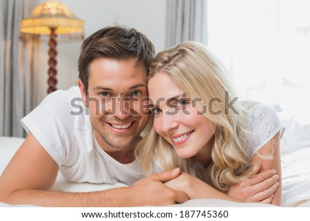 Portrait of a relaxed happy casual young couple resting in bed at home - stock photo