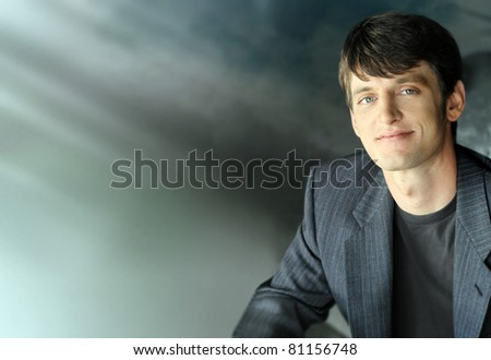 Portrait of a relaxed happy young businessman with cool modern background and lots of copy space - stock photo