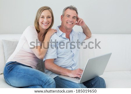 Portrait of a relaxed loving couple using laptop on sofa at home