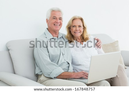Portrait of a relaxed loving senior couple using laptop on sofa in a house