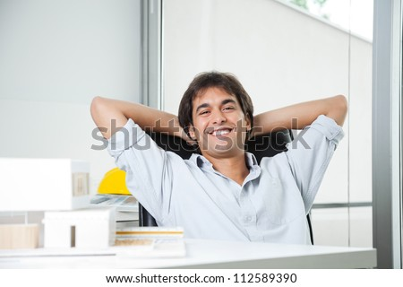 Portrait of a relaxed male architect sitting in chair with hands behind head - stock photo