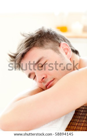Portrait of a relaxed man lying on a massage table in a spa center