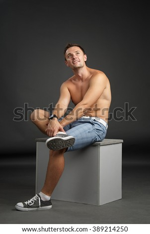 Portrait of a relaxed man sitting on a cube
