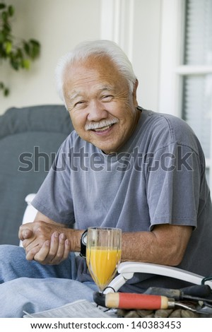 Portrait of a relaxed smiling senior man with orange juice