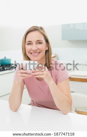 Portrait of a relaxed smiling woman having coffee in the kitchen at home