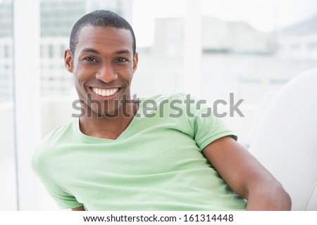 Portrait of a relaxed smiling young Afro man in a bright house - stock photo
