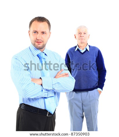 Portrait of a relaxed son standing with his father behind against white background - stock photo