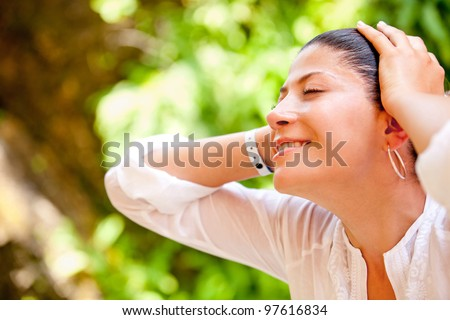 Portrait of a relaxed woman outdoors enjoying nature - stock photo