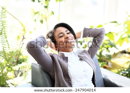 Portrait of a relaxed young businesswoman sitting  in a bright office - stock photo