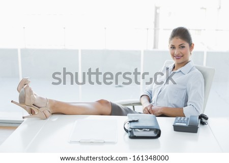 Portrait of a relaxed young businesswoman sitting with legs on desk in a bright office