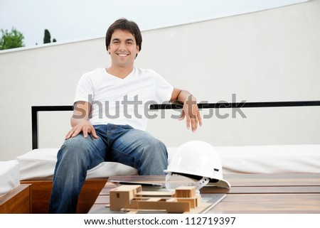 Portrait of a relaxed young male architect with hardhat and model structure on table