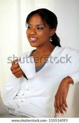 Portrait of a relaxed young woman holding a white mug while sitting pensive on couch at home indoor