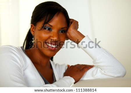 Portrait of a relaxed young woman sitting on couch at home indoor
