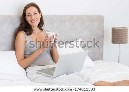 Portrait of a relaxed young woman using laptop in bed at home