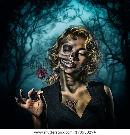 Portrait of a retro woman with skull make-up and dried flowers in her hand in the night forest - stock photo