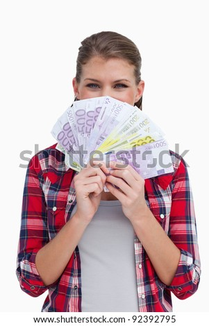 Portrait of a rich woman holding bank notes against a white background - stock photo