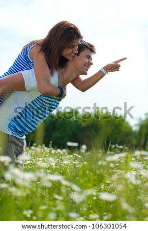 Portrait of a riding happy smiling couple: handsome young man pointing & holding beautiful young woman outdoors on a bright sunny day of spring or summer on the green garden or park background - stock photo