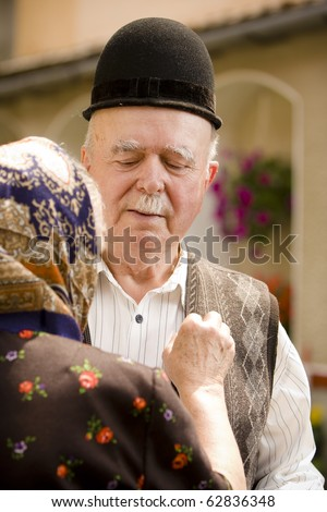 Portrait of a romanian traditional very old couple on country side. Focus on the man's face expression. See more images with them. - stock photo