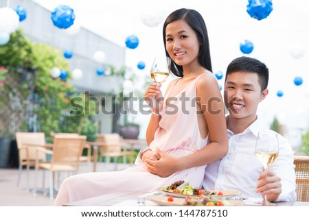 Portrait of a romantic couple celebrating their relationship, girl sitting on the guy�¢??s lap - stock photo