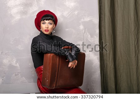 Portrait of a romantic Frenchwoman beret. A girl holding a suitcase. The concept of French fashion. - stock photo
