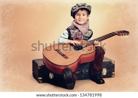 Portrait of a romantic little boy sitting with his guitar. Retro style. - stock photo