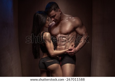 Portrait of a Romantic Young Bodybuilding Couple with Sexy Bodies Posing so Closed Against a Brown Wooden Wall Background - stock photo